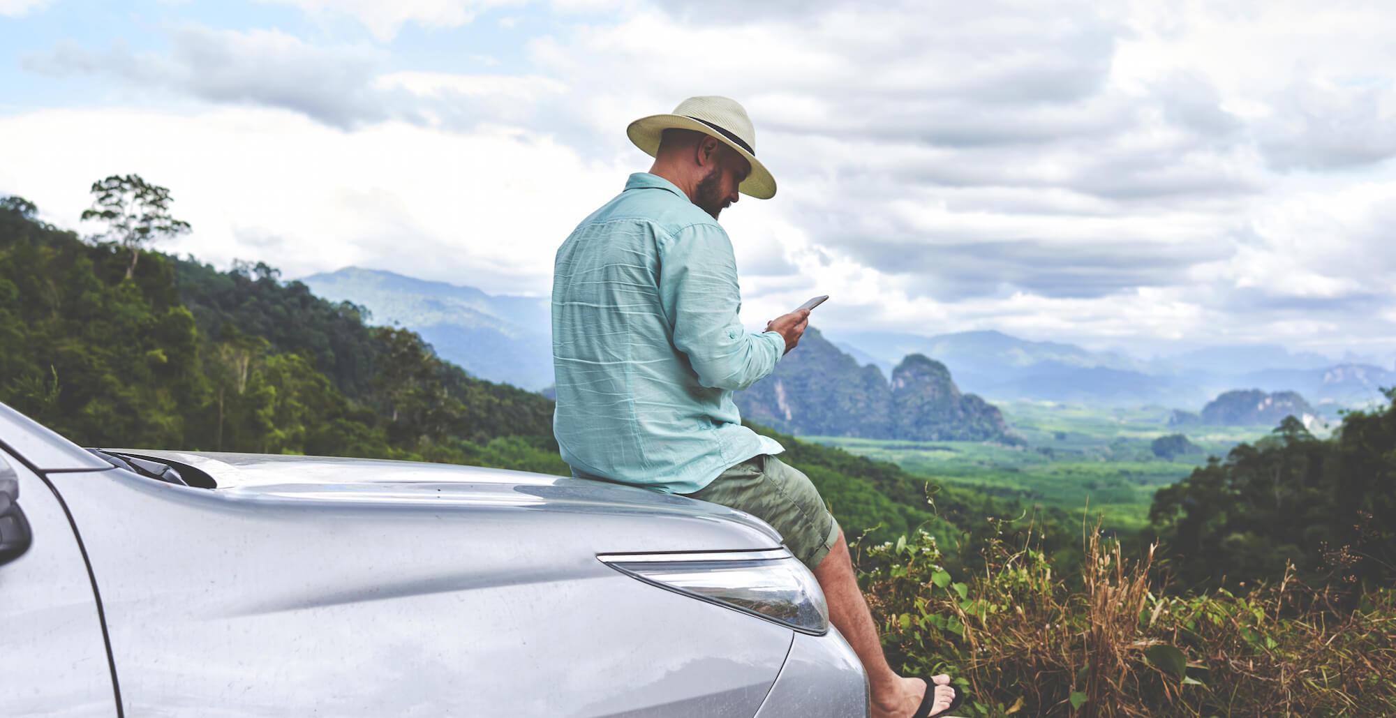 man making phone call on car hood