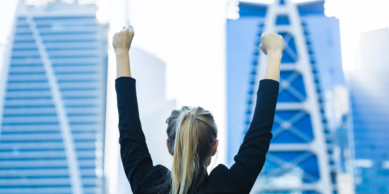 business woman celebrating among city buildings