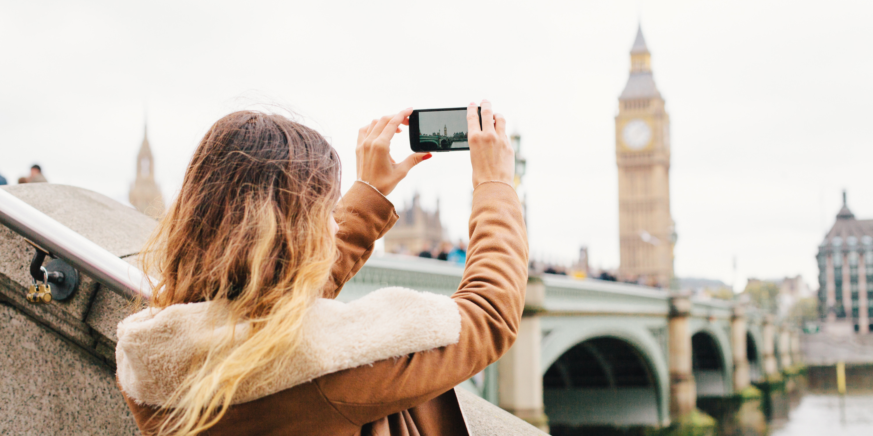 young woman taking picture of Big Ben on phone