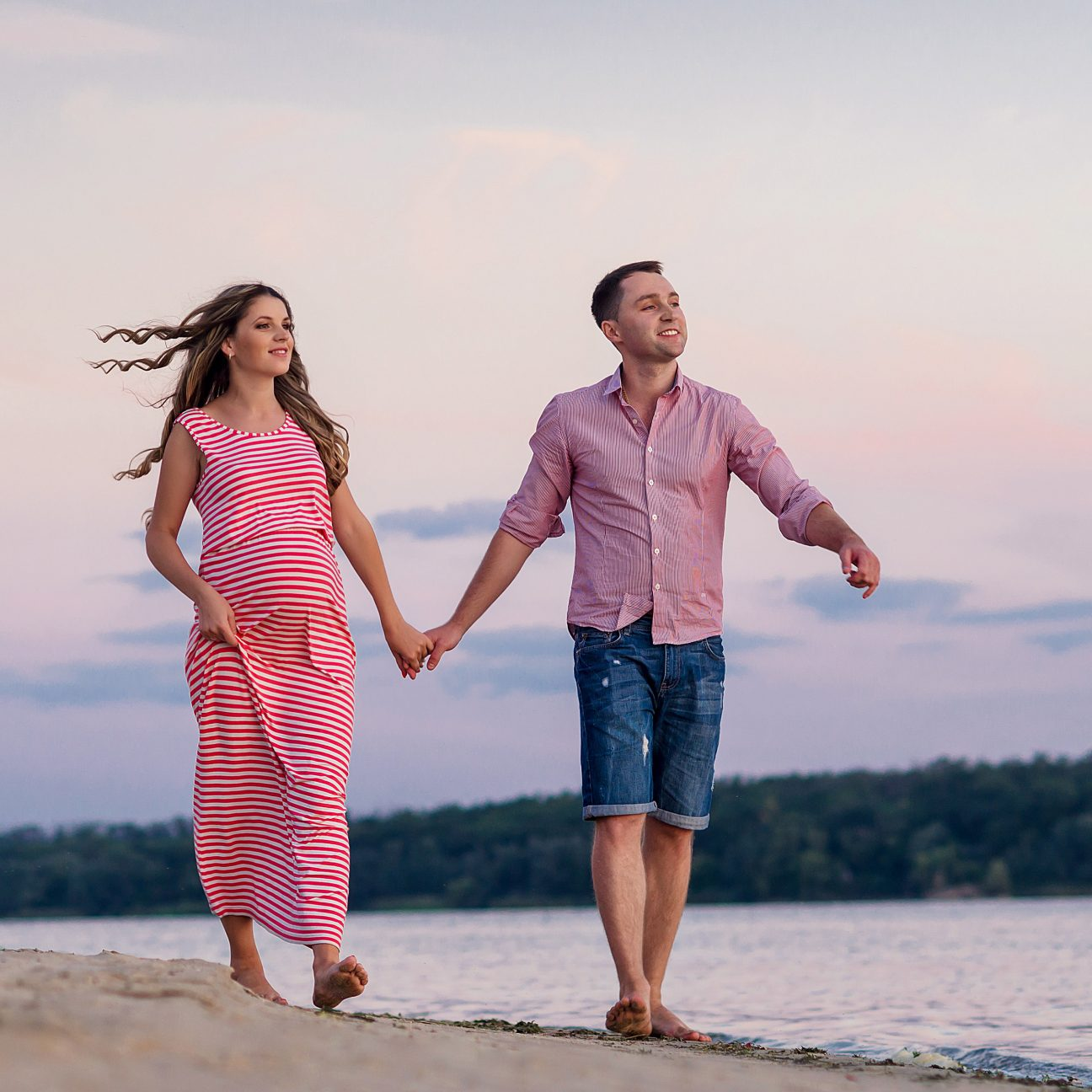 pregnant couple walking on beach at sunset