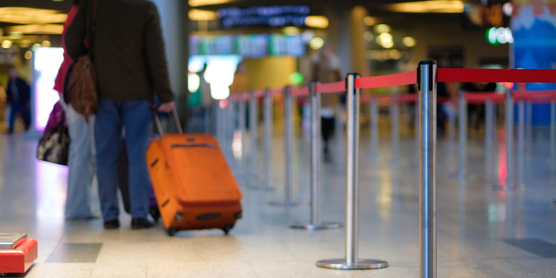 traveler walking through TSA precheck with baggage