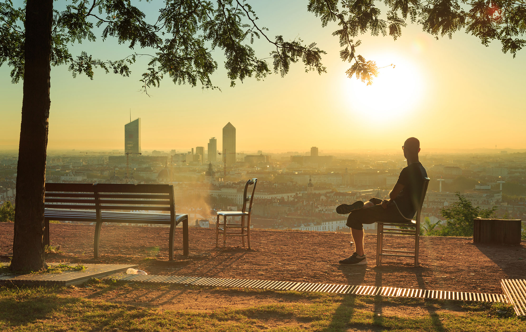 Person sitting on chair facing sunset