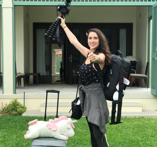 woman standing with stuff unicorn and camera