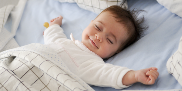 Smiling baby sleeping on blue sheets