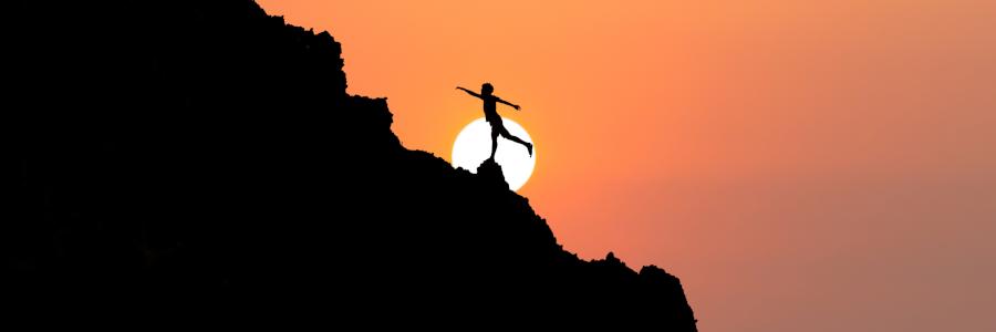 woman doing yoga pose on mountain side
