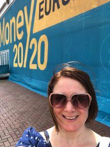 Megan posing in front of Money 20/20 sign