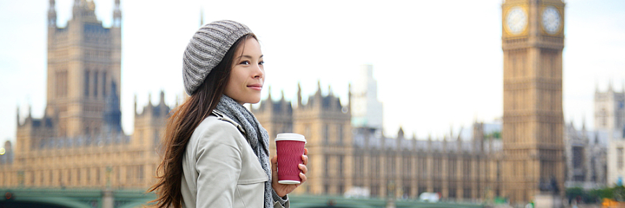 dual citizenship. Woman Holds Coffee in Front of Westminster Palace