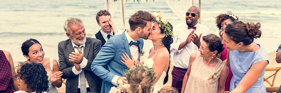 Couple Kisses Surrounded by Friends at Beach Wedding Ceremony The most affordable international wedding destination locations