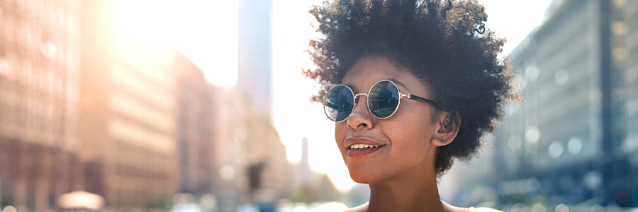 Person with sunglasses smiling and standing against cityscape — self-employment