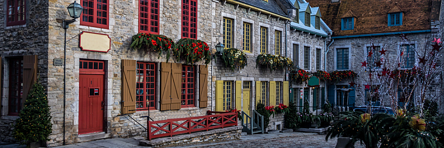 Grey stone houses with coloured shutters in a row in Québec City